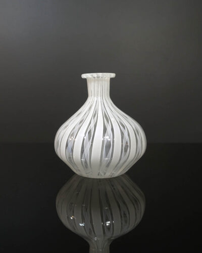"Stout shaped mouth-blown vase with finely rolled opening. About 4 inches tall. Fine white Latticino cane fillagree designs run vertically. There are occasional small bubbles, a result of the handmade glassblowing process called ""Zanfirico"". Similar designs were produced by Venini from Murano, Italy."